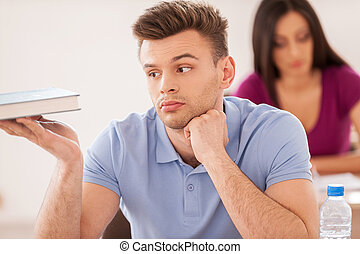 Bored student. Handsome male student holding hand on chin and looking at the textbook while young woman sitting at the desk behind him