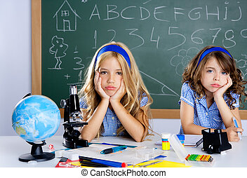 Bored student kids at school classroom in desk with blackboard
