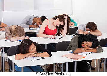 Bored Student With Classmates Sleeping At Desk