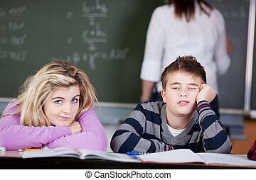 Bored Students Leaning On Desk With Teacher In Background