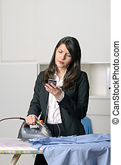 Bored unhappy housewife doing the ironing staring off to the side with a glum expression while simultaneously checking emails on her smart phone
