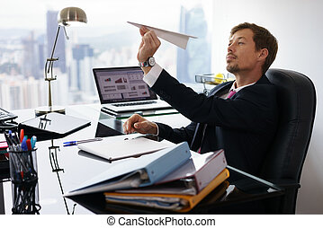 Bored White Collar Worker Throwing Paper Airplane In Office...