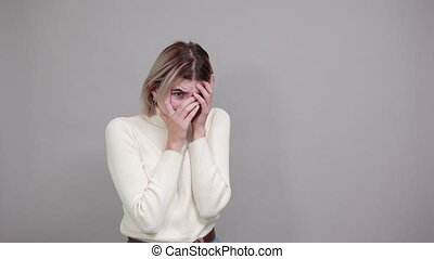 Bored woman in casual clothes looking through fingers, with hand behind head