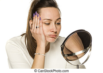 bored woman looking at herself in the mirror