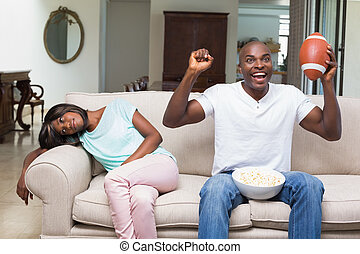 Bored woman sitting next to her boyfriend watching football