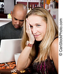 Bored woman with man on laptop computer