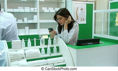 Bored young pharmacist broqsing via mobile phone at work place