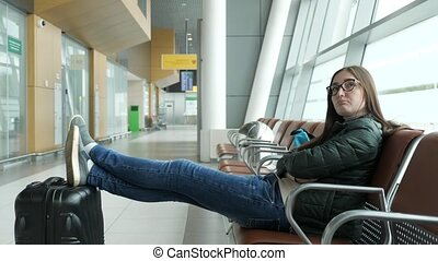 Bored young woman is waiting her flight in airport sitting in hall.