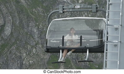 Bored young woman riding a cable car in mountains - Woman...
