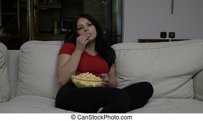 Bored young woman sitting on the couch and eating popcorn while watching TV in the evening