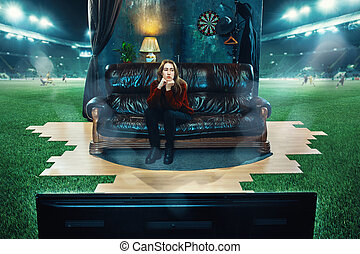 Boring fan is sitting on the sofa and watching TV in the middle of a football field.