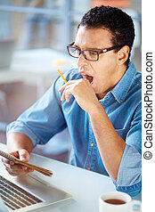Businessman with notepad and pencil yawning at workplace