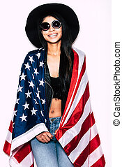 Born to be free. Beautiful young mixed race woman carrying American flag on shoulders and smiling while standing against white background