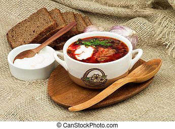 Borscht. Traditional Soup with Beet, Vegetables, Meat Arranged with Brown Bread, Garlic and Sour Cream on Wooden Plate with Wooden Spoon