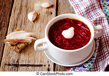borscht with sour cream on the wooden background