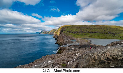 Bosdalafossur waterfall on Vagar island coastline wide...
