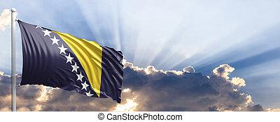 Bosnia and Herzegovina flag on blue sky. 3d illustration -...