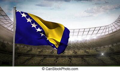 Bosnia and Herzegovina national flag waving on flagpole in football stadium with flashes