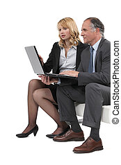 Boss and employee looking at laptop