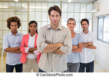 Boss and employees looking at camera in the office
