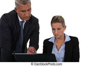 Boss and secretary looking at laptop screen