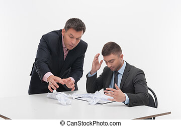 Boss angry with young employee sitting at desk - Senior and ...