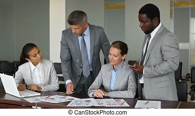 Boss - Experienced boss reviewing financial reports of his...