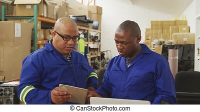 Front view of a mixed race male supervisor and an African American male worker in a storage warehouse at a factory making wheelchairs, standing and talking at a workbench, the supervisor using a tablet and his colleague using a laptop computer