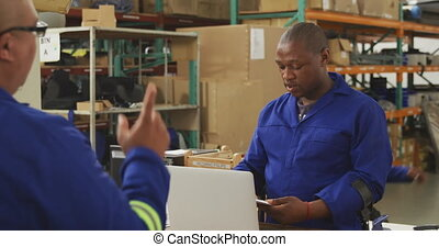 Front view of an African American male worker and a mixed race male worker in a storage warehouse at a factory making wheelchairs, standing and talking across a counter, one man passing the other a clipboard and giving some instructions. The man behind the counter is standing on crutches