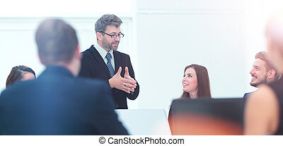 boss holds a conversation with the employees of the company...