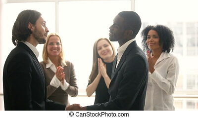 Boss promoting rewarding african american male employee, congratulating shaking hands