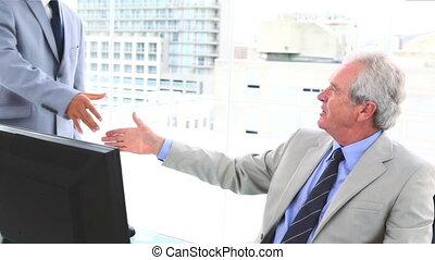 Boss shaking a businessman hand