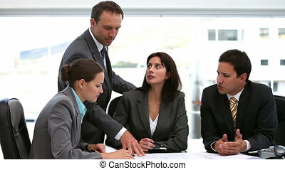 Boss showing his employees a document during a meeting in an office