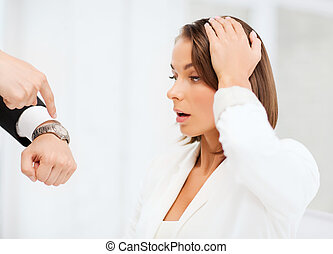 boss showing time to stressed businesswoman - business and...