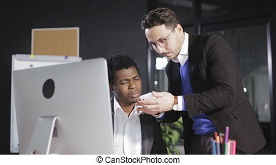 Boss shows his employee a pictures on the smartphone in the office