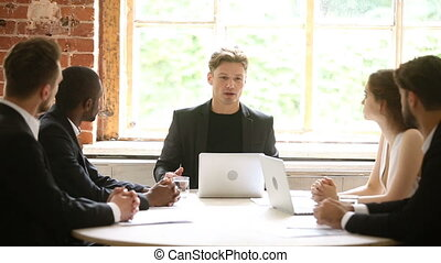 Boss talking to diverse team giving instructions at group meeting