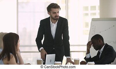 Boss talking with diverse company members during meeting in...