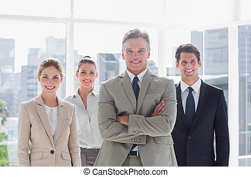 Boss with his arms folded standing with smiling colleagues