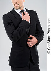 Bossy men. Bossy young men adjusting his necktie while standing isolated on grey