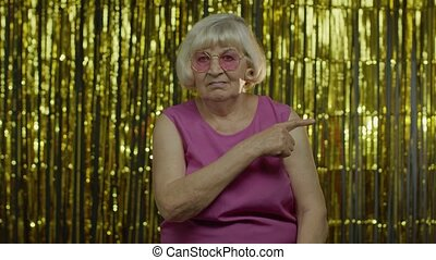 Bossy strict senior old blond woman in pink blouse blaming and asking to get out, conflict, break-up. Elderly grandma. Studio shot isolated on foil fringe golden curtain background. 6k resolution shot