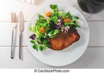 boston butt steak with fresh leaf salad. top view