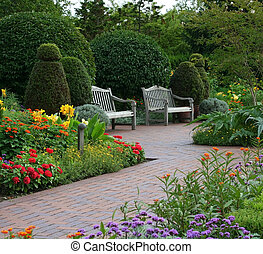 Two benches are surrounded by flowers and plants.