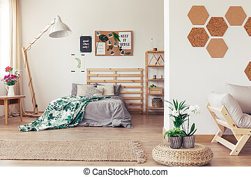Wooden bed and couch in botanic open interior with cork honeycomb wall, jute rug, rattan pouf and green plants