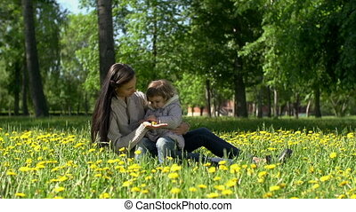 Botanic Studies - Mother and daughter sitting in grass,...