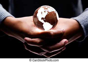 America continent - both hands holding a glass globe on it...