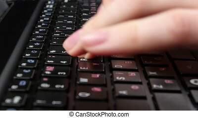 Both hands of an office worker typing on black keyboard, close up
