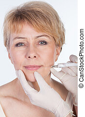 Botox injection in lips - Middle aged woman receiving a...