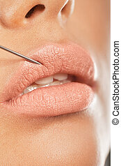 Botox Injection In The Lip. Closeup of a needle giving...