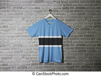 Botswana flag on shirt and hanging on the wall with brick pattern wallpaper.