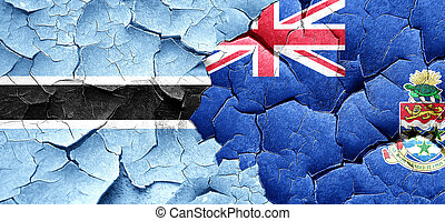 Botswana flag with Cayman islands flag on a grunge cracked wall